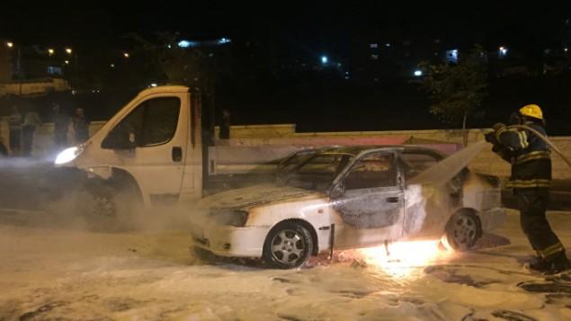 رجال الإطفاء يعملون على إطفاء سيارة مشتعلة بعد تعرضها لزجاجة حارقة بالقرب من حي بيت حنينا في القدس الشرقية، 3 أغسطس، 2015. (Sliman Khader/Flash90)