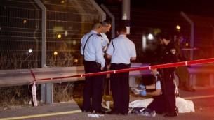 قوات الأمن الإسرائيلية تقف بجانب جثمان الفلسطيني انس طه الذي طعن اسرائيلي بمحطة بنزين على شارغ 443، 9 اغسطس 2015 (Yonatan Sindel/Flash90)