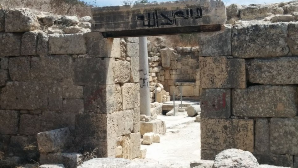 """كنيسة القديس يوحنا المعمدان في سبسطية بالضفة الغربية، كُتب على أحد عمدانها """"لا إله إلا الله"""" بالعربية. (Ilan Ben Zion/Times of Israel staff)"""