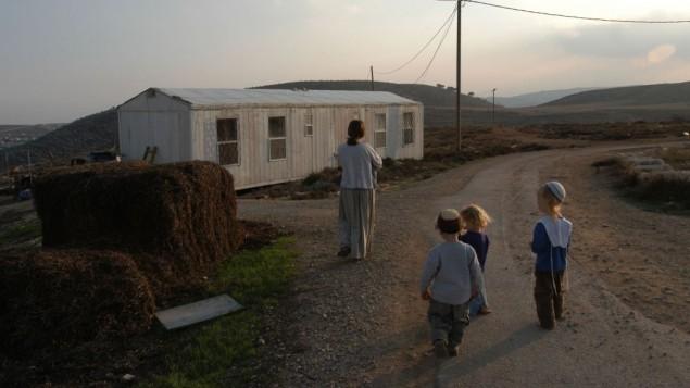 """صورة توضيحية لعائلة تسير في بؤرة """"عادي عد"""" الإستيطانية، 27 نوفمبر، 2003. (فلاش 90)"""