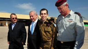 """الجندي الإسرائيلي المحرر غلعاد شاليط (الثاني من اليمين) يسير إلى جانب رئيس الوزراء بينيامين نتنياهو (الثاني من اليسار)، ووزير الدفاع في ذلك الوقت إيهود باراك (من اليسار)، ورئيس هيئة أركان الجيش الإسرائيلي في ذلك الوقت بيني غانتز (من اليمين)، في قاعدة """"تل نوف"""" الجوية جنوب إسرائيل، 18 أكتوبر، 2011. ((Ariel Hermoni/Defense Ministry/Flash90)"""
