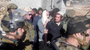 مئير إتينغير، يضع قبعة بيضاء، يرافقه الجنود الإسرائيليين إلى خارج قرية قصرة في الضفة الغربية، 7 يناير، 2014. (حاخامات من أجل حقوق الإنسان)