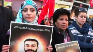 شيرين عيساوي، تحمل صورة شقيقها الأسير المضرب عن الطعام سامر، اثناء مظاهرة دعم (screen capture: YouTube)