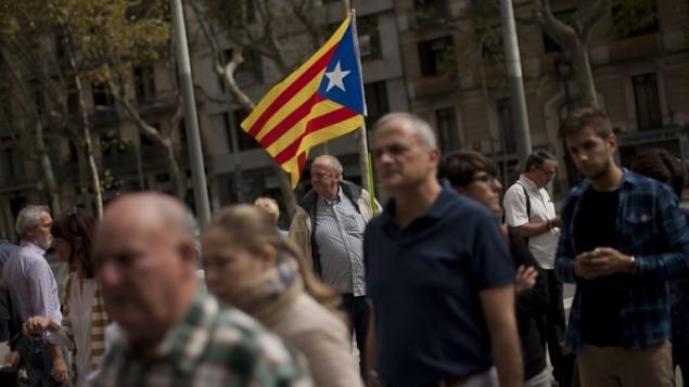 رجل يرفع علم استقلال كتالونيا بينما يتجه السكان للتصويت في انتخابات محلية مبكرة في برشلونة، 27 سبتمبر 2015 (JORGE GUERRERO / AFP)
