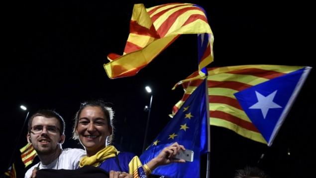 مؤيدون لإستقلال كتالونيا يحتفلون ملوحين بالأعلام الأوروبية والكتالونية بعد إغلاق صناديق الإقتراع خلال الإنتخابات الإقليمية الكتالونية في 27 سبتمبر، 2015 في برشلونة. (AFP PHOTO / GERARD JULIEN)