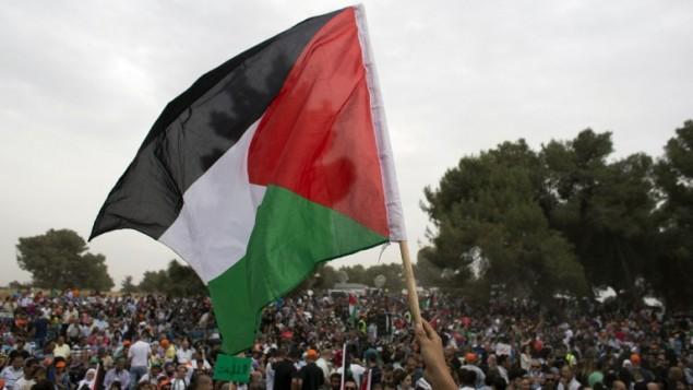 صورة توضيحية لرفع علم فلسطين (AFP/Ahmad Gharabli)