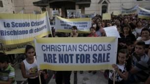 مئات المسيحيين مواطني إسرائيل يرفعون لافتات في مسيرة إحتجاجية ضد ما يصفونه بالتمييز التي تمارسه الدولة في تمويل مدارسهم في ساحة كنيسة البشارة في الناصرة، 1 سبتمبر، 2015 (Ahmad Gharabli/AFP)