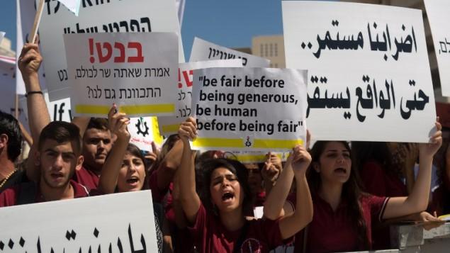 طلاب من المدارس الأهلية المسيحية يرفعون اللافتات خلال تظاهرة إحتجاجية للمطالية بمزيد من التمويل لمدارسهم، 6 سبتمبر، 2015 في القدس. (Menahem Kahana/AFP)