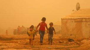 أطقال سوريون يسيرون وسط الغبار خلال خلال عاصفة رملية في 7 سبتبمر، 2015 في مخيم للاجئين على مشارف مدينة بعلبك شرقي لبنان. (AFP Photo/STR)