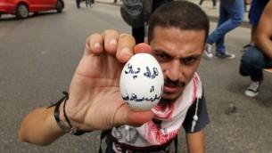 """ناشط لبناني يحمل بيضة مكتوب عليها """"هدية من الشعب"""" قبل ان يرميها على موكب سياسيين مشاركين بجولة حوار وطني في مركز بيروت، 9 سبتمبر 2015 (ANWAR AMRO / AFP)"""