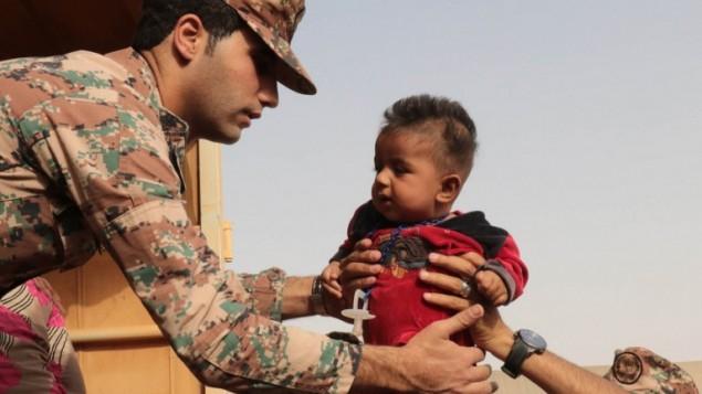 جندي اردني يحمل طفل سوري لاجئ في مخيم لاجئين مؤقت بالقرب من الحدود الاردنية السورية، 10 سبتمبر 2015 (KHALIL MAZRAAWI / AFP)
