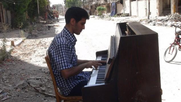 (ارشيف) ايهم الاحمد يعزف البيانو بين انقاض مخيم اليرموك للاجئين الفلسطينيين في ريف دمشق، 26 يونيو 2014 (RAMI AL-SAYED / AFP)