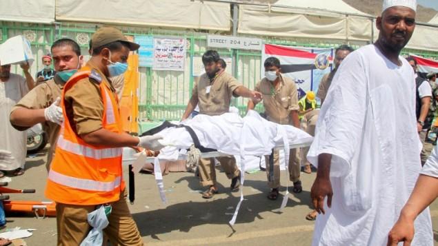 عمال طوارئ سعوديون ينقلون جثة من موقع حادثة التدافع التي راح ضحيتها أكثر من 700 شخص في منى، القريبة من مدينة مكة المكرمة، خلال موسم الحج السنوى في السعودية، 24 سبتمبر، 2015. (AFP PHOTO / STR)
