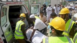 عمال طوارئ سعوديون وحجاج يقومون بإدخال مصاب إلى داخل سيارة إسعاف في موقع حادثة التدافع التي راح ضحيتها أكثر من 700 شخص في منى، القريبة من مدينة مكة المكرمة، خلال موسم الحج السنوى في السعودية، 24 سبتمبر، 2015. (AFP PHOTO / STR)