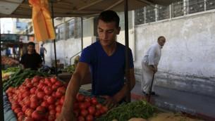 معمر قويدر يبيع الخضروات في بسطته في مدينة غزة، 29 سبتمبر 2015 (MOHAMMED ABED / AFP)