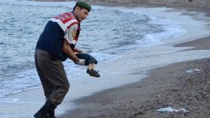 شرطي تركي يحمل جثة طفل سوري في شاطئ بدرم، جنوب تركيا، 2 سبتمبر 2015 (AFP/DOGAN NEWS AGENCY)