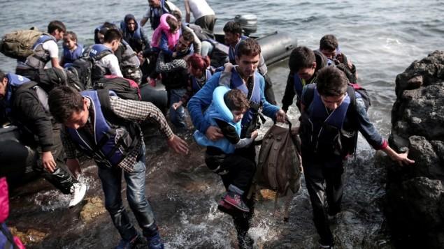 """لاجئون سوريون يصلون إلى شواطئ جزيرة """"ليسبوس"""" اليونانية بعد رحلة في قارب منفوخ عبر بحر إيجة من تركيا، 3 سبتمبر، 2015. (AFP/ANGELOS TZORTZINIS)"""