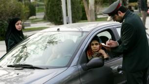 (ارشيف) شرطي ايراني يوقف سيارة اثناء حملة لفرض قوانين اللباس الشرعي في شمال طهران، 22 ابريل 2007 (BEHROUZ MEHRI / AFP)