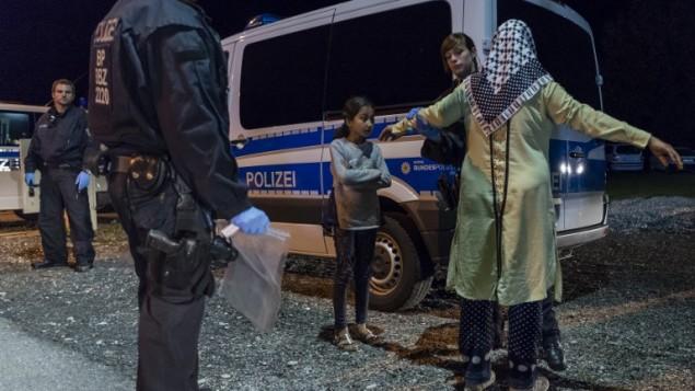 شرطية توقف لاجئة وابنتها على الحدود النمساوية الالمانيةـ 14 سبتمبر 2015 (GUENTER SCHIFFMANN / AFP)