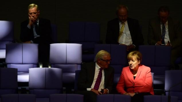 المستشارة الالمانية انجيلا ميركل تتحدث مع وزير الخارجية الالماني فرانك فالتر شتاينماير بعد مخاطبة البرلمان في برلين، 25 سبتمبر 2015 (JOHN MACDOUGALL / AFP)