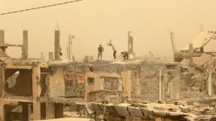 عمال بناء يعملون بين الحطام في قطاع غزة خلال عاصفة رملية، 9 سبتمبر 2015 (MAHMUD HAMS / AFP)