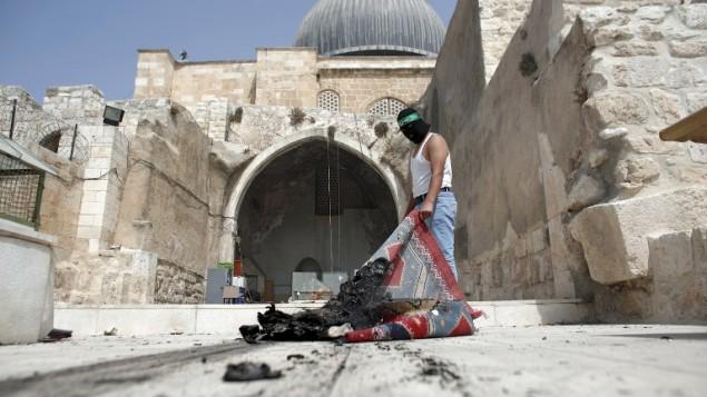 شاب فلسطيني ملثم يضع عصابة رأس تحمل شعار حركة حماس يقوم بإخراج بساط محترق من مسجد الأقصى في البلدة القديمة في القدس خلال مواجهات في الموقع قي 13 سبتبمر، 2015، ساعات قليلة فقط قبل بدء الإحتفالات بالسنة العبرية الجديدة، 13 سبتبمر، 2015. (AFP PHOTO/AHMAD GHARABLI)