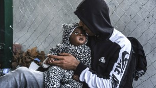 رجل يقبل طفله بينما ينتظر على الحدود بين المجر وصربيا، 15 سبتمبر 2015 (ARMEND NIMANI / AFP)