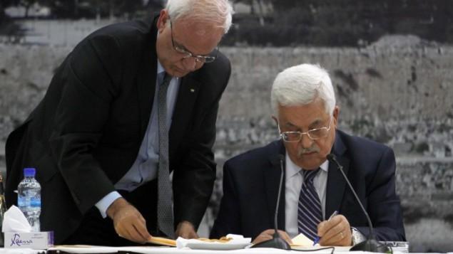 رئيس السلطة الفلسطينية محمود عباس، من اليمين، يوقع على طلب الإنضمام إلى 15 هيئة مرتبطة بالأمم المتحدة ومعاهدات دولية أخرى في المقاطعة في رام الله بالضفة الغربية يوم الثلاثاء، 1 أبريل، 2014. إلى جانبه يقف صائب عريقات. (Issam Rimawi/Flash90)