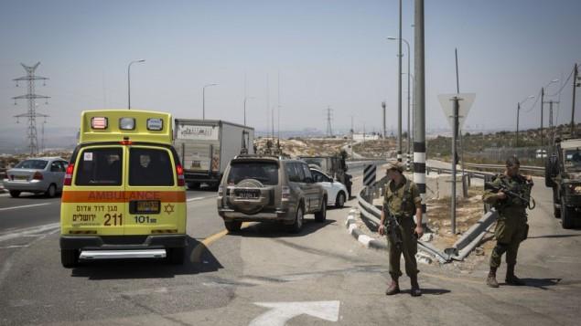 """سيارة إسعاف تقوم بإجلاء  رجل فلسطيني أُصيب بجراح طفيفة بعد تعرضه لإطلاق النار بعد طعنه لجندي إسرائيلي في حاجز """"بل""""، على طريق رقم 443، 15 أغسطس، 2015. (Hadas Parush/Flash90)"""