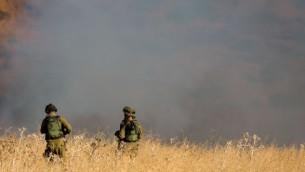 جنود إسرائيليون يقفون بالقرب من حريق كبير خارج 'كفار سولد' في هضبة الجولان والذي نشب جراء إطلاق 4 صواريخ من الجانب السوري على الحدود الإسرائيلية-السورية في 20 أغسطس، 2015. (Basel Awidat/Flash90)