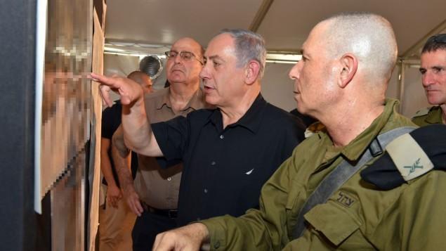 بينيامين نتنياهو، في الوسط، ووزير دفاعه موشيه يعالون، في الخلفية، مع مسؤولين عسكريين خلال زيارة إلى الحدود الجنوبية لإسرائيل مع الأردن في 6 سبتمبر، 2015. (Ariel Hermoni/Defense Ministry)