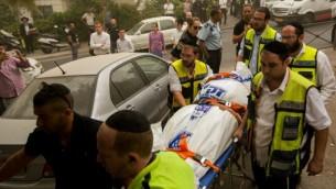 """طاقم من """"زاكا"""" يحمل حثة في حي """"روميما"""" في القدس، حيث تم العثور على زوجين ميتين جراء إستنشاقهما للغاز، الثلاثاء، 8 سبتمبر، 2015. (Yonatan Sindel/Flash90)"""