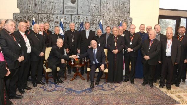 الرئيس رؤوفين ريفلين (يجلس في الوسط من اليمين) في مقر إقامته مع أعضاء  من مجلس المؤتمرات الأسقفية الأوروبية، يصافح رئيس المجلس الكاردينال بيتر إردو في القدس، 16 سبتمبر، 2015. (Michael Nyman/GPO)
