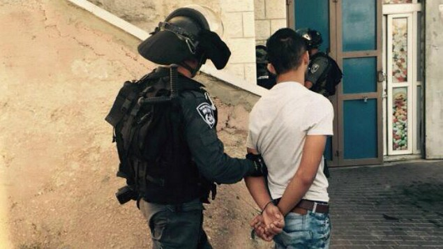 """عناصر من حرس الحدود يعتقلون شابا فلسطينيا بعد مواجهات في حي """"جبل المكبر"""" في القدس في 18 سبتمبر، 2015، والتي أسفرت عن إصابة 3 رجال شرطة وأحد المحتجين. (الشرطة الإسرائيلية)"""