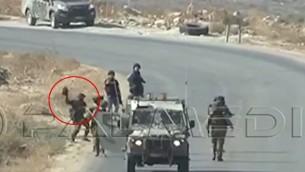 صورة التقطت من شريط فيديو في الضفة الغربية يظهر جندي اسرائيلي يرمي ما يبدو انها كاميرا تابعة لصحفيين في وكالة فرانس برس، 25 سبتمبر 2015 (screen capture: YouTube)