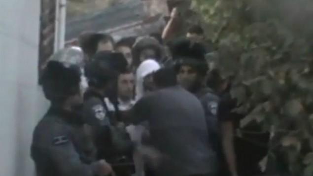 قوات الأمن الإسرائيلية ترافق طلاب معهد ديني من منزل فلسطيني في الخليل في 3 أغسطس، 2015، حيث قام رجل فلسطيني بتوفير ملجأ لهم بعد أن أثار تواجدهم في المدينة أعمال شغب. (لقطة شاشة: موقع NRG)