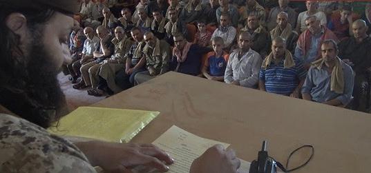 عناصر تنظيم 'الدولة الإسلامية' يجبرون المسيحيين في مدينة 'القريتين' السورية على التوقيع على عقد لغير المسلمين، في صورة تم نشرها في 3 سبتبمر، 2015. ( MEMRI)