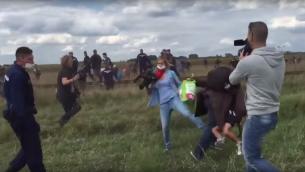 """مصورة قناة """"ان1تي في"""" المجرية تركل مهاجر يحمل طفل اثناء فراره من الشرطة (screen capture: YouTube)"""