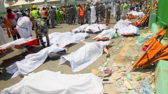عمال طوارئ وحجاج  يقفون بجانب جثث مغطاة في موقع حادثة التدافع التي راح ضحيتها أكثر من 700 شخص في منى، القريبة من مدينة مكة المكرمة، خلال موسم الحج السنوى في السعودية، 24 سبتمبر، 2015. (AFP PHOTO / STR)