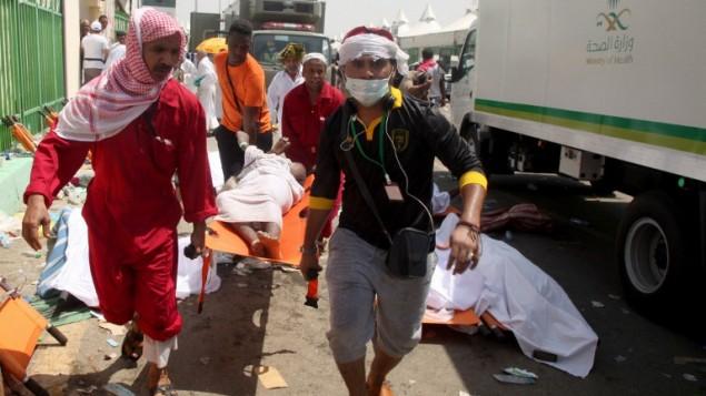 عمال طوارئ سعوديون وحجاج يحملون شخصا مصابا في الموقع حيث قُتل المئات في تدافع في منى، بالقرب من مدينة مكة خلال  موسم الحج السنوي في السعودية، 24 سبتمبر، 2015. (AFP/ STR)
