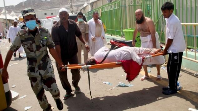 حجاج وعامل طوارئ سعوديون يحملون سيدة على نقالة في موقع حادثة التدافع  في منى التي راح ضحيتها المئات، بالقرب من مدينة مكة المكرمة، خلال موسم الحج السنوي في السعودية، 24 سبتمبر، 2015. (AFP/STR)
