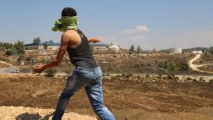 فلسطيني من بلدة النبي صالح في الضفة الغربية يرشق الجنود الإسرائيليين بالحجارة، 28 اغسطس 2015 (Eric Cortellessa/Times of Israel)