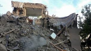 رجل افغاني يبحث بين انقاض منزل مدمر بعد زلزال بقوة 7,5 درجة، 26 اكتوبر 2015 (STR / AFP)