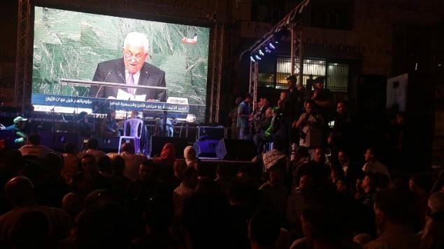 فلسطينيون يتابعون خطاب رئيس السلطة الفلسطينية محمود عباس على شاشة عملاقة في رام الله خلال الكلمة التي ألقاها أمام الجمعية العامة للأمم المتحدة في مقر المنظمة في نيويورك، 30 سبتمبر، 2015. (AFP/Jaafar Ashtiyeh)