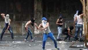 شبان فلسطينيون يلقون الحجارة باتجاه قوى الأمن الإسرائيلية خلال مواجهات في مدينة الخليل بالضفة الغربية، 4 أكتوبر، 2015. (AFP/Hazem Bader)