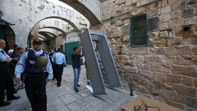 قوات الأمن الإسرائيلية توفر الحراسة خلال قيام عمال بوضع جهاز كشف معادن في الحي الإسلامي في البلدة القديمة بمدينة القدس، 8 أكتوبر، 2015، في أعقاي تصاعد هجمات الطعن بالسكين. ( AFP Photo / Gali Tibon)