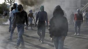 ملثمون راشقو حجارة فلسطينيين  خلال اشتباكات مع قوات الأمن الإسرائيلية في بيت ايل (مستوطنة يهودية)، شمالي مدينة رام الله في الضفة الغربية  9 أكتوبر 2015 AFP PHOTO / ABBAS MOMANI