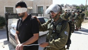 قوات الأمن الإسرائيلية تعتقل فلسطيني خلال مواجهات في قرية بيت عمر القريبة من مدينة الخليل، في الضفة الغربية، 11 أكتوبر، 2015. (AFP/Hazem Bader)