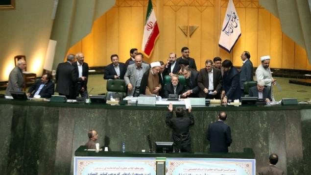 رئيس مجلس الشورى الإيراني علي لاريجاني يستمع الى نائب خلال جلسة تصويت حول الاتفاق النووي الموقع مع الدول الكبرى، 13 اكتوبر 2015 (MEGHDAD MADADI / TASNIM / AFP)