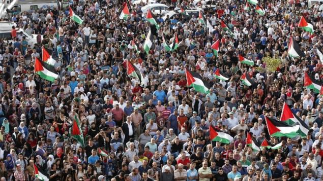 """عرب اسرائيليون يحملون الاعلام الفلسطينية اثناء مظاهرة قطرية ضخمة ضمن """"يوم الغضب"""" الفلسطيني في مدينة سخنين في شمال اسرائيل، 13 اكتوبر 2015 (JACK GUEZ / AFP)"""
